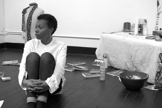 Photograph of a woman sitting on the ground, her knees held to her chest, gazing into the distance. Behind her on a black, wooden floor, objects such as books, candles, a bottle of Jack Daniels, and a bowl are strewn. In the right-hand corner of the frame, more candles and various artifacts sit atop a table covered in white tablecloth. Just behind the woman, a patterned scarf is draped around the neck of an upright torso of a mannequin.