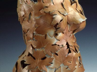 A ceramic sculpture in the shape of a torso, from clavicle to hips, made out of leaves. The warm brown leaves are layered, but don't entirely cover the torso, leaving gaps where you to see into the sculpture.