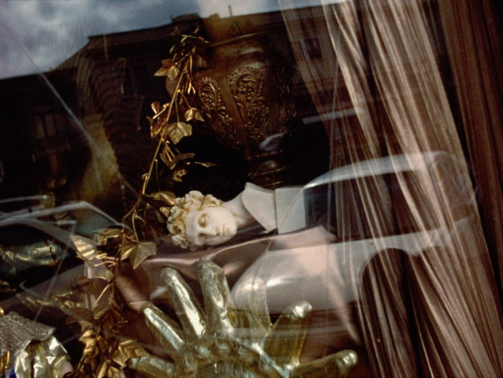A film still showing a view through a window. Behind the window, a white sculpture of a man's head in the style of Ancient Greek sculpture lies on its side on a table covered in a taupe, satiny cloth. A large, shiny, gold object that could be a sculpture of a sun shape sits below it, cut off by the bottom of the frame. The scene outside the window reflects in it, creating a surreal compression of space.