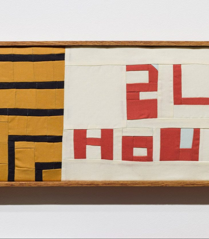 """The text """"24 HOURS"""" in red is stitched into a quilt using fabric and thread, with black and yellow lines protruding to the left, imitating a neon sign. All displayed in reclaimed oak frame."""