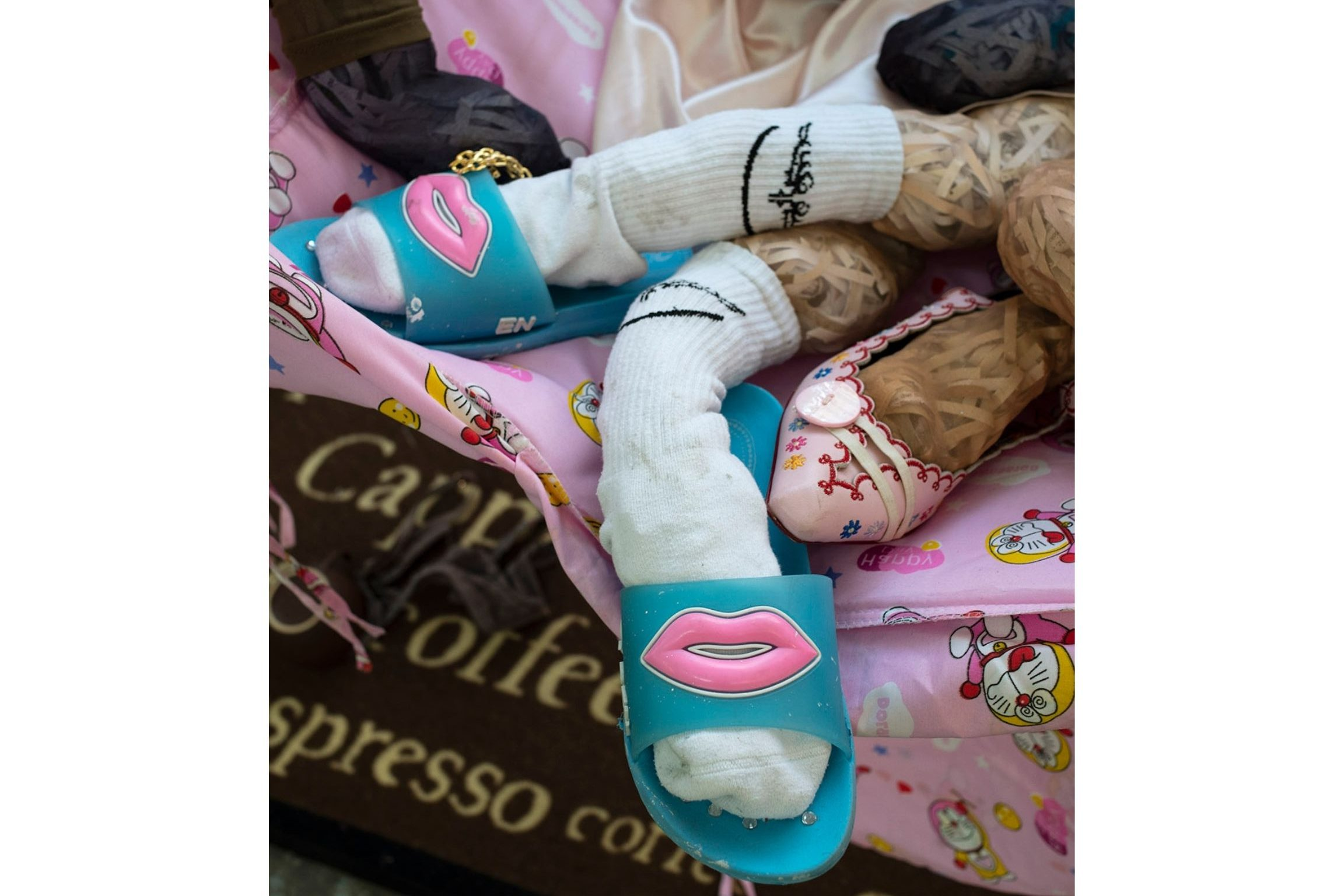 """Photograph of """"legs,"""" which are pantyhose stuffed with shreds of paper, wearing ankle socks and blue sandals with a pink graphic of lips on them."""