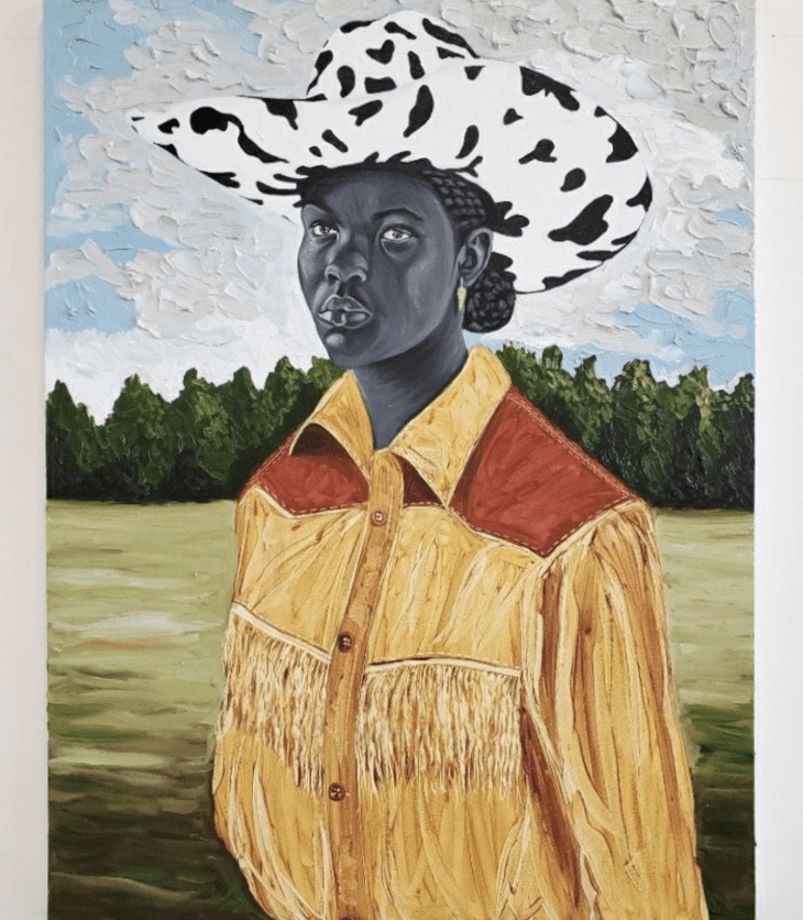 Portrait of a Black woman wearing gold earrings, her hair pulled behind her head and tucked into a cow-print cowboy hat. She wears a yellow western fringe shirt and stands before a field, abutted by a treeline.