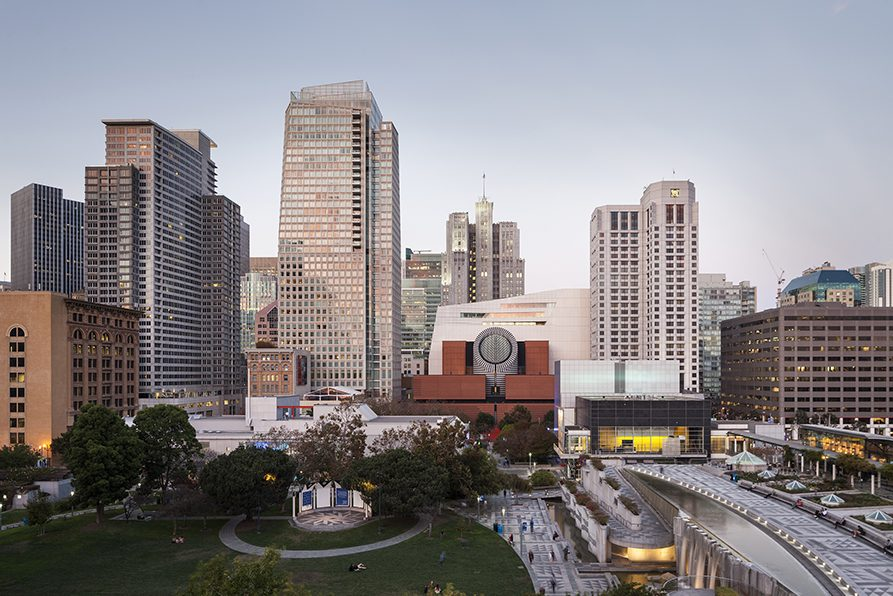 Photograph of San Francisco skyline from the Yerba Buena Gardens, just before dusk. Folks are scattered across the lawn, walking down the sidewalk. Warms lights in high-rise windows are just beginning to flicker on.