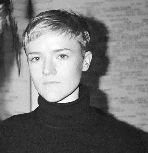 A black and white image of Claire Mullen, a woman with light skin and a blonde pixie cut, who is wearing a black turtleneck sweater and looking directly into the camera, without smiling.