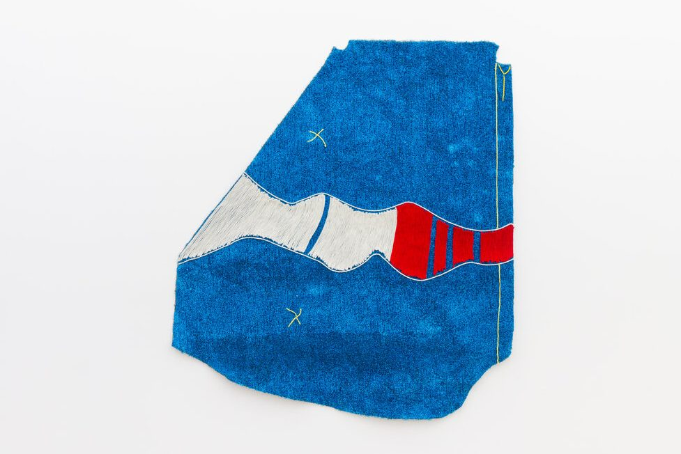 An object floats before a vapid white background, colored red, white, and blue, the irregular shape which seems to be cut from cloth evokes vague images of the American West, staking flags in hard soil, stitching together uniforms.