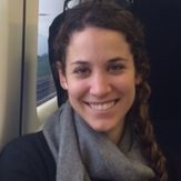 Grace Linden is on a train. She is a light skinned women with brown curly hair. She is grinning.