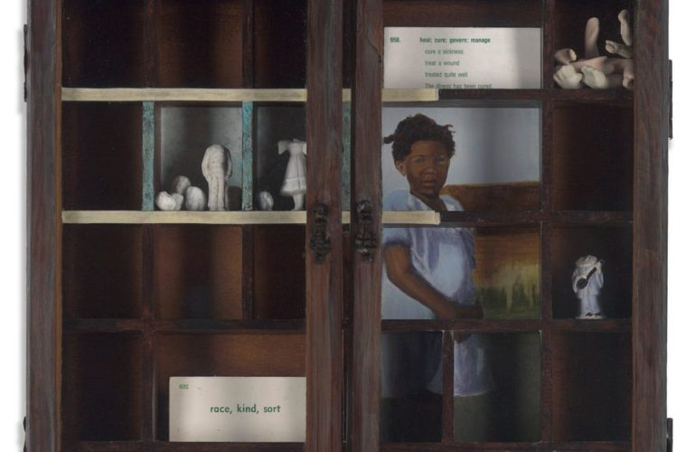 """A cabinet contains a few small items: the heads and arms of tiny figures, a painting of a black woman in a blue dress, a white car that reads """"race, kind, sort."""""""