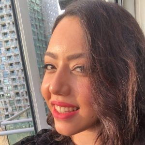 Selfie of Nadine Nour el Din sitting on her balcony in London. She is a woman in her thirties with mid-length wavy brown hair. She is smiling at the camera