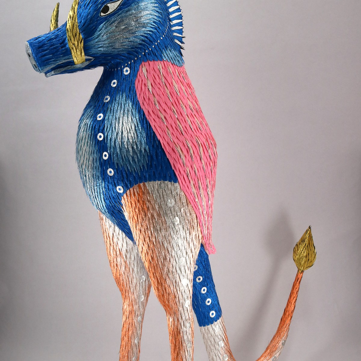 A beast, adorned with bright blue, pink and silver scales, stands upright with its front legs crossed behind its back, its tail flared behind it like obedient coat tails and its tusks curved skyward, glimmering gold. Its ears are pointed and eyes set forward.
