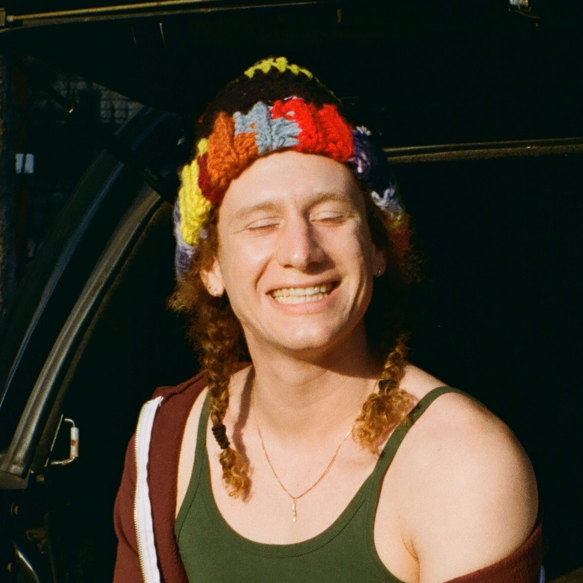 Johnny sitting on the tailgate of a car next to a surfboard in Brooklyn, NY. They have their hair in braids under a colorful knit cap, smiling big with their eyes closed.