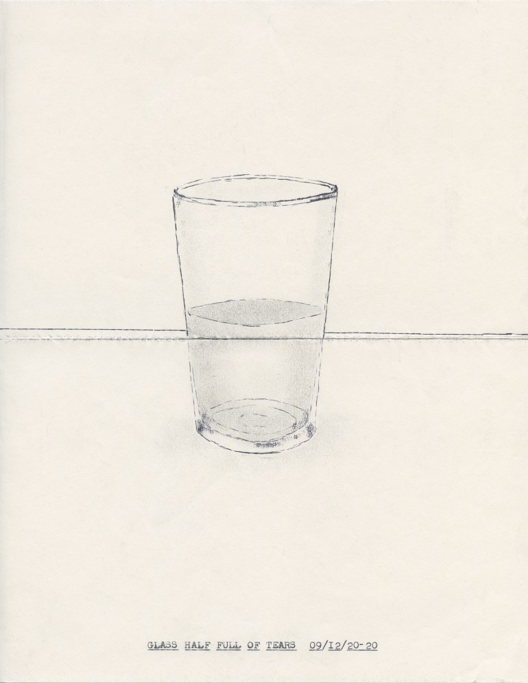 """A glass, half filled with a grey something, rests on a table. The words """"GLASS HALF FULL OF TEARS 09/12/20-20"""" populate the bottom of this piece of sketch paper."""