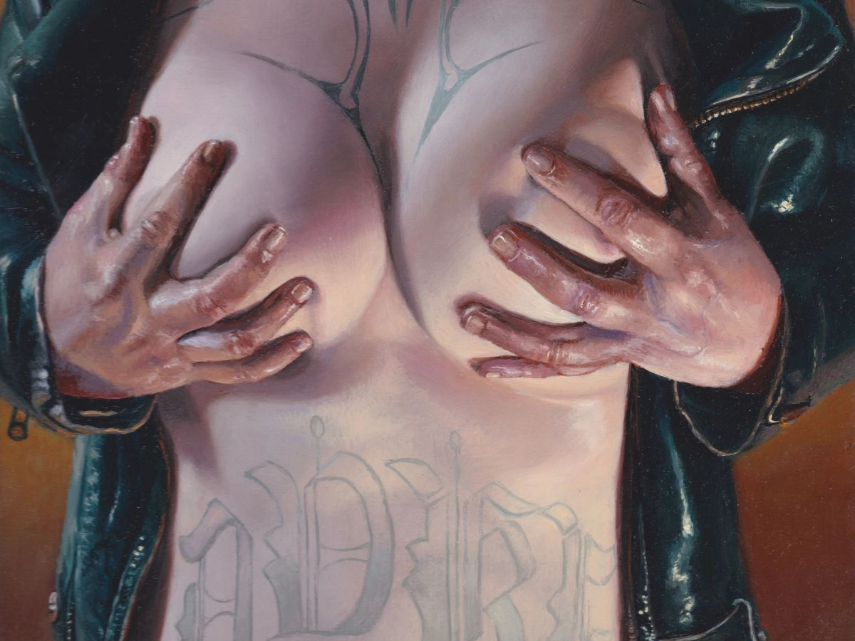 An individual holds their breasts in their hands, the tattoos on their their chest and stomach exposed as a leather jacket is drawn open, like a curtain.