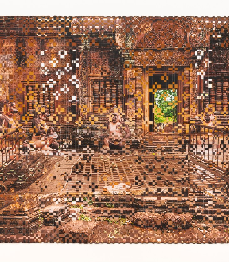 A photograph of a metal bed frame with a straw pillow, situated before an open temple door, is distorted by countless, missing sections removed from it, like missing puzzle pieces or an image half-loaded.