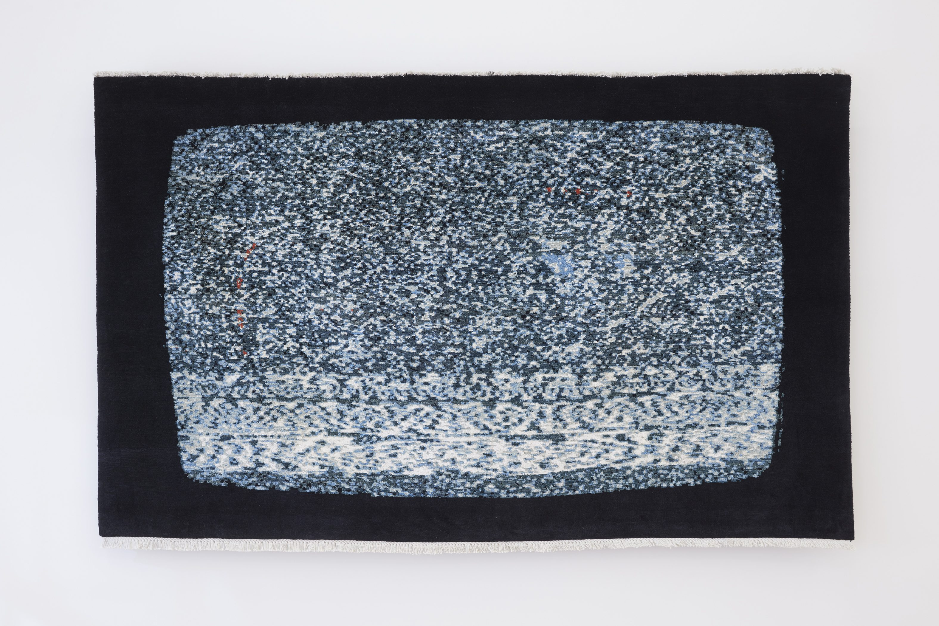 A large tapestry hanging on a white wall evokes a large T.V., registering only black and white static.
