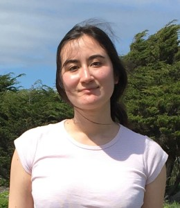 Janine Sun Rogers standing in front of some Monterey cypress trees. She is a woman in her 20s with fair skin and dark brown hair in a low ponytail, wearing a pale pink T-shirt. She is smiling calmly at the camera and her hair is blowing in the wind.