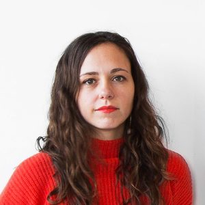 Headshot of Elizabeth Arzani She is a woman in her thirties with long wavy brown hair. She is wearing a red sweater and red lipstick; looking at the camera without smiling.
