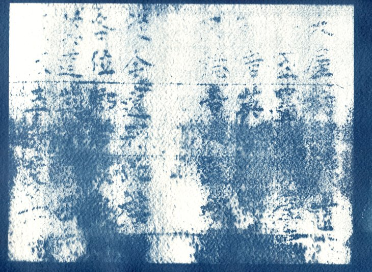 The memory of pressed letters in a vertical columns fade into the background of a worn letter press.