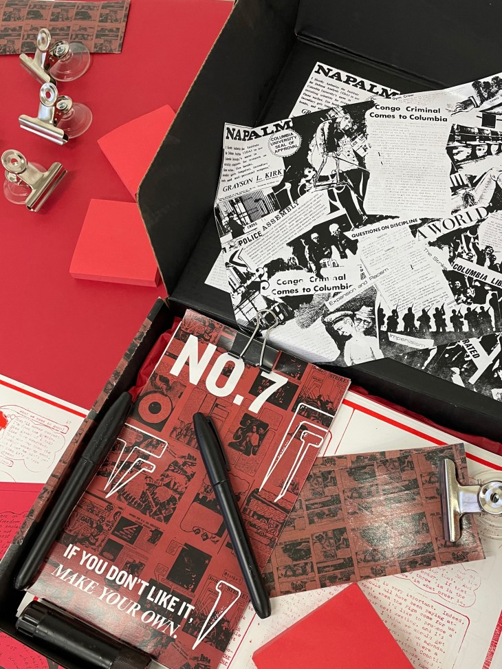 """An open box on red tablecloth holds collaged newspaper clippings, a stack of pamphlets titled """"No.7 If you don't like it, make your own"""" and other assorted objects."""