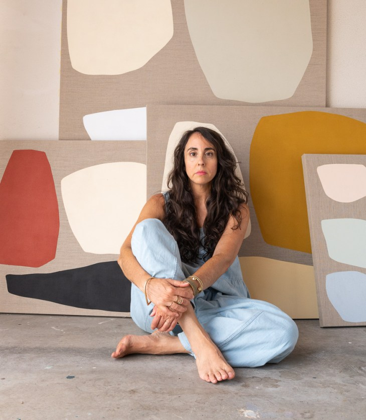 Woman with long, wavy-brown hair is seated with crossed legs before her artwork—four different sized pieces with blocks and blobs of color leant against a white wall.