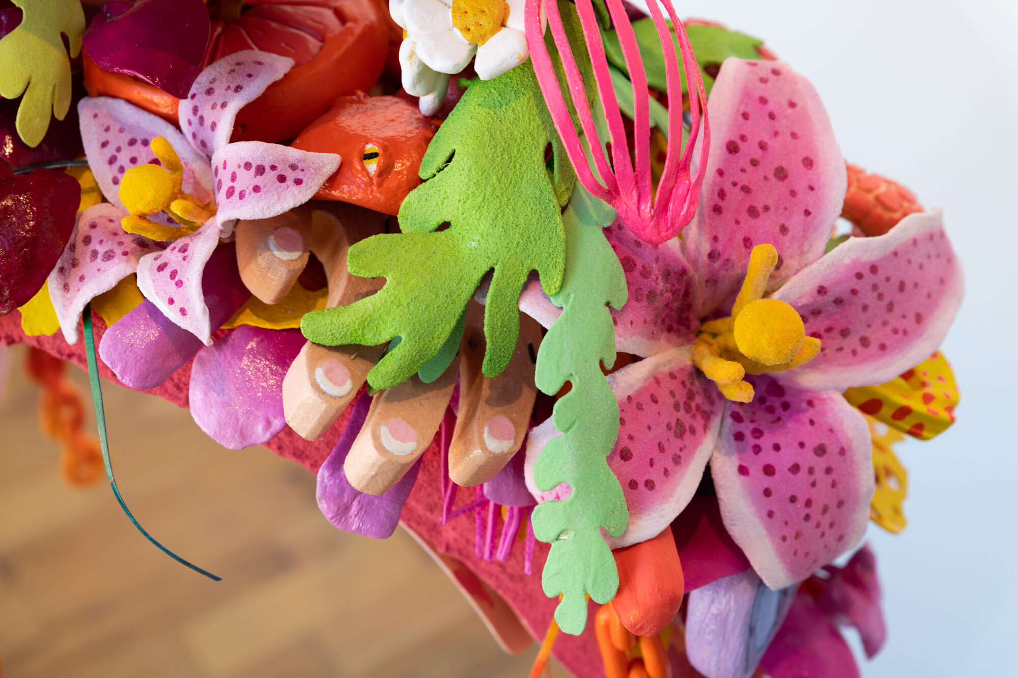 Cartoonish and vibrant layers of flowers, seaweed, fingers, and figures make up this closeup arched arm of a statue.