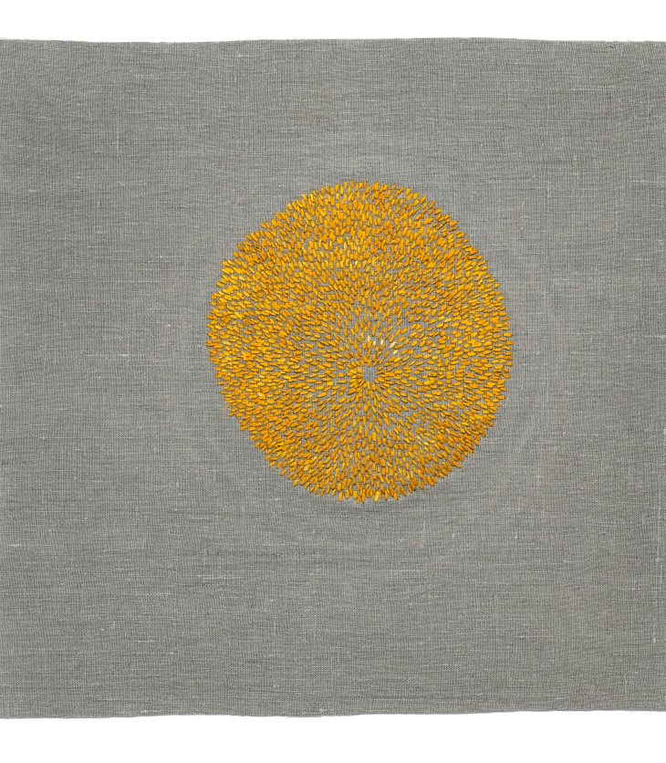 Near the center of a woven grey canvas, small, knitted yellow buds flower outwards to form a circle.