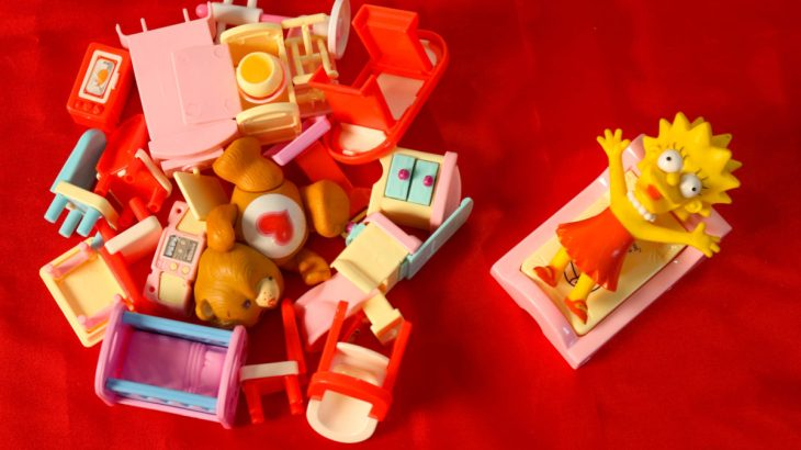 On the right, a toy figure reclines on a toy bed; on the left, a pile a small toy objects, including a teddy bear, a few chairs, a dresser, etc. lay in a pile—all before a red background.
