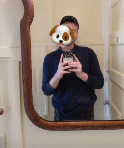 T Reckling taking a selfie in a mirror while walking down the stairs. They are a masc genderqueer person in their twenties with pale skin and short brown hair. A puppy emoji covers their face as they live with body and gender dysphoria.