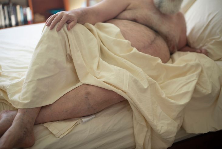 A figure lies on their side, a cream colored sheet draped over their midsection, their hand on their knee and their white beard out of focus and half out of frame.