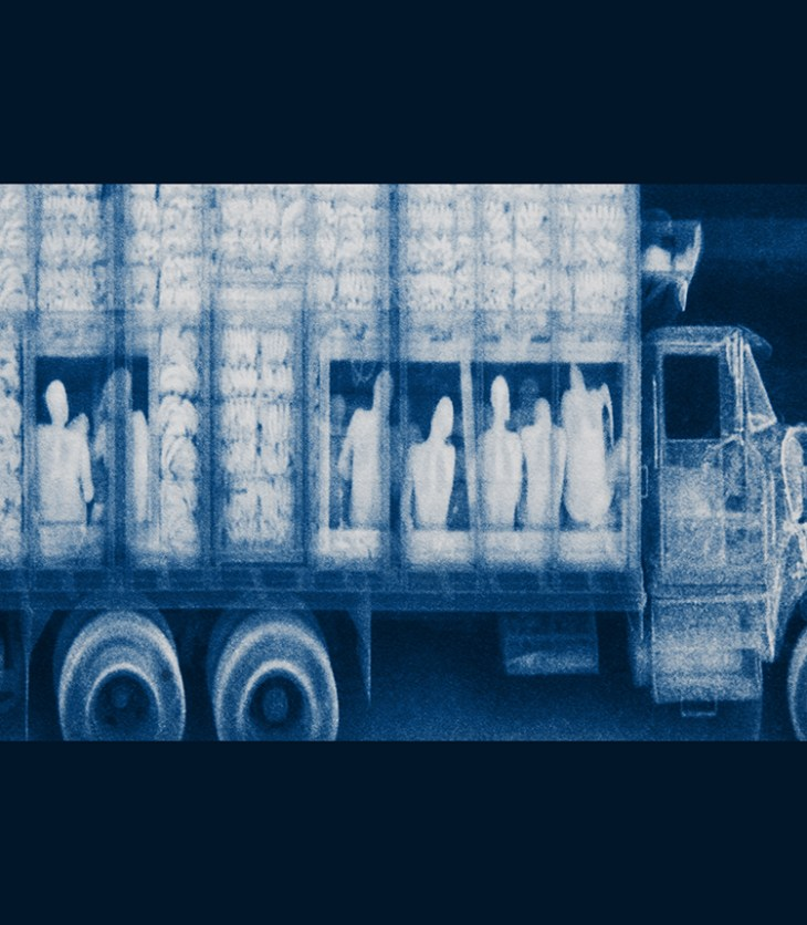 In the bed of a large truck, otherwise full of bananas, X-ray imaging technology reveals multiple hidden, cramped bodies stuffed beneath the other cargo, awash in the digital haze of blue.