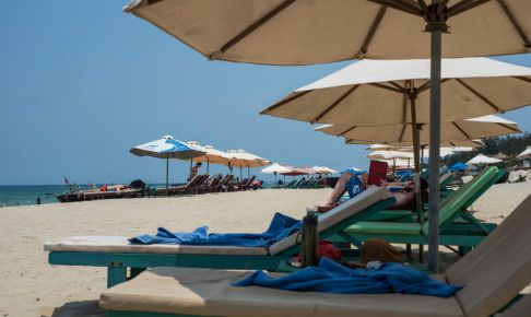 Tourists relax on long chairs under large umbrellas on a beach of Hoi An, Viet Nam.