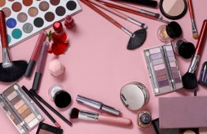 makeup brushes and cosmetics on a pink background. professional set.