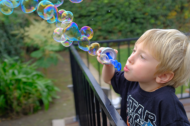 Grandson blowing bubbles
