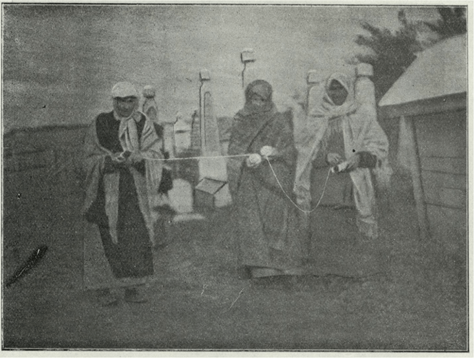 Three women holding a length of string in a Jewish cemetery, practising feldmestn