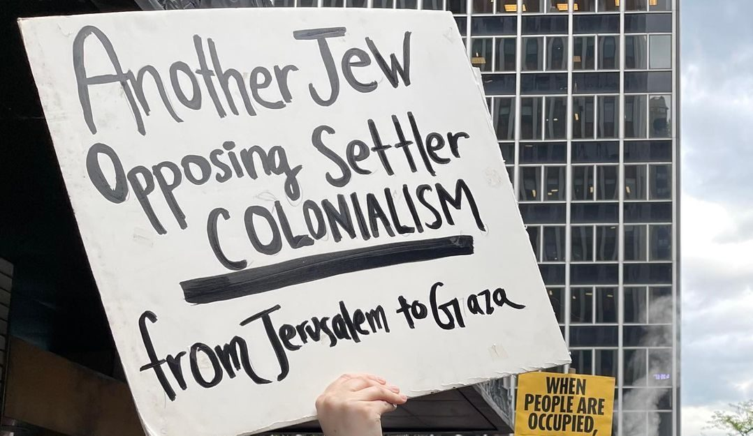 A woman in a protest crowd holds up a sign that reads: 'Another Jew opposing settler colonialism from Jerusalem to Gaza'