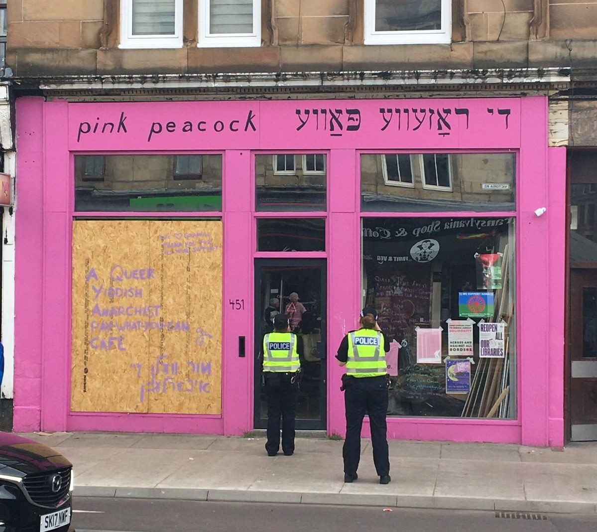 A pink shopfront with the sign 'Pink Peacock' and one boarded up window, with two police officers stood outside