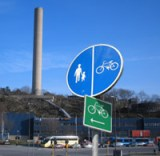 Cykelskylt med Värmdövägen och Henriksdals reningsverk i bakgrunden