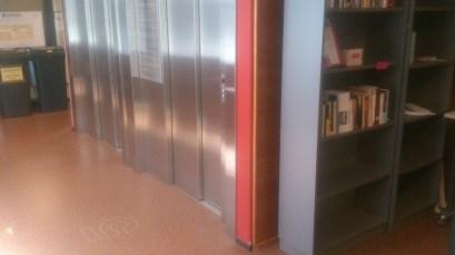 Hissien vieressä, nurkan takana. Next to the lifts round the corner.