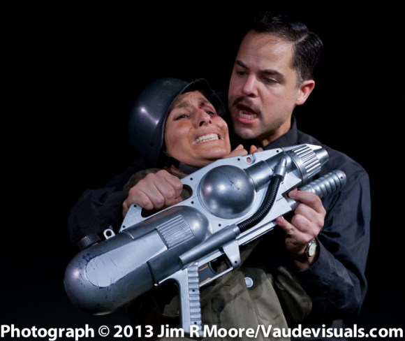The General tries to convince the new recruit (Madeleine Sierra) to use the 'big' gun.