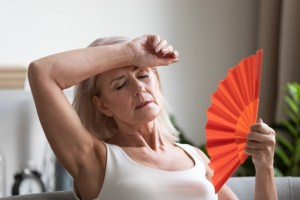 middle aged woman fanning herself due to hot flashes