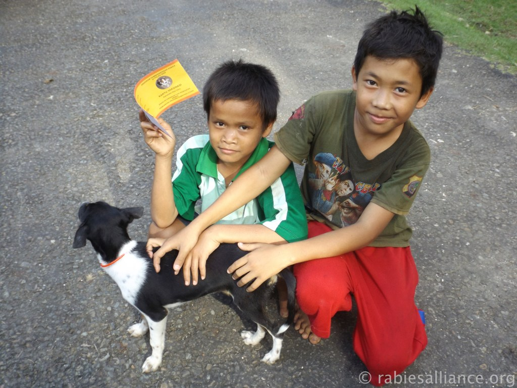Two Indonesian boys proudly show off their puppy and her vaccination record.