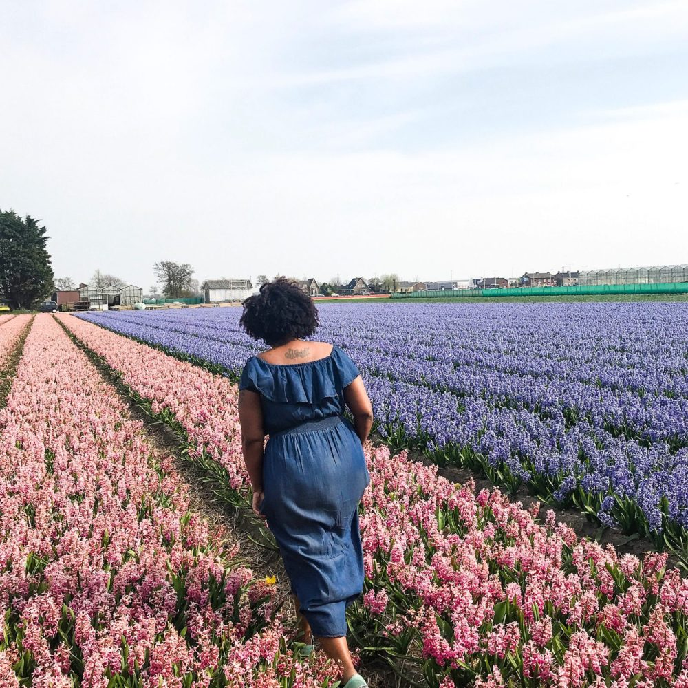 Black woman walking through a field of flowers in Lisse, Netherlands