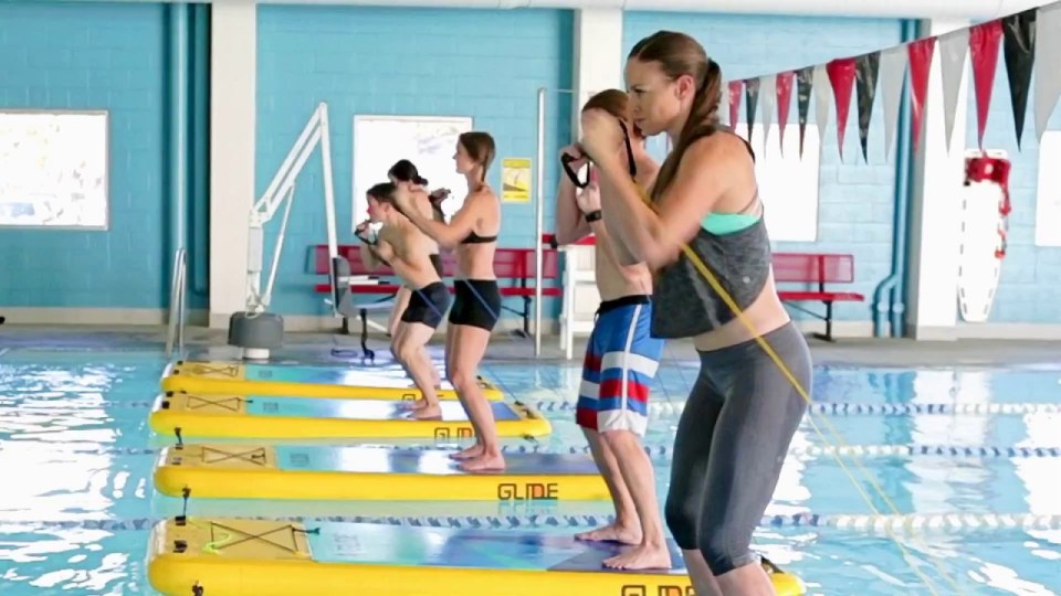 people learning in water Pilates class on floating boards in pool