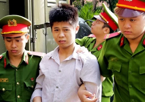 Nguyen Huu Tinhis escorted by police officers to the court where he receives death penalty for murders. Photo by VnExpress/Ky Hoa.
