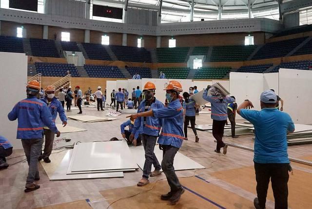 Đơn vị thi công gấp rút xây dựng, lắp đặt khu điều trị Covid-19 tại Cung thể thao Tiên Sơn. Ảnh: Lê Bảo.