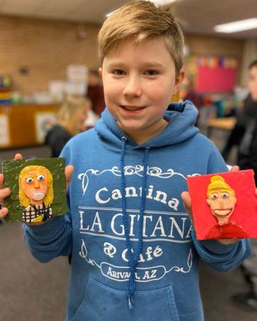 Học sinh Roe Battershell khoe hai bức tranh do em tự thực hiện. Ảnh: Emily Nitcher/ The World Herald.