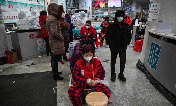 Người dân ngồi đợi kiểm tra sức khỏe ở Bệnh viện Hội Chữ thập đỏ Vũ Hán, tỉnh Hồ Bắc. Ảnh: AFP.