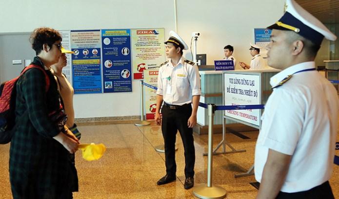 Nhân viên y tế của Trung tâm Kiểm dịch y tế quốc tế theo dõi thân nhiệt khách Trung Quốc qua máy tín