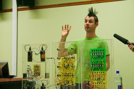 This man makes musical instruments out of electrical motors and relays. I think his hair got like that when he plugged the machine into his ear by accident.