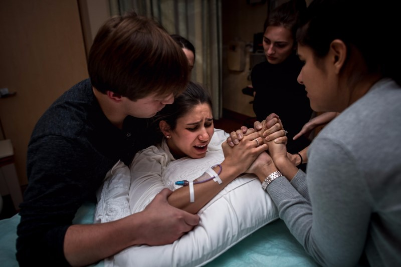 Birthing Woman in Hospital Supported by Husband, Doula, and Other Birth Team Members