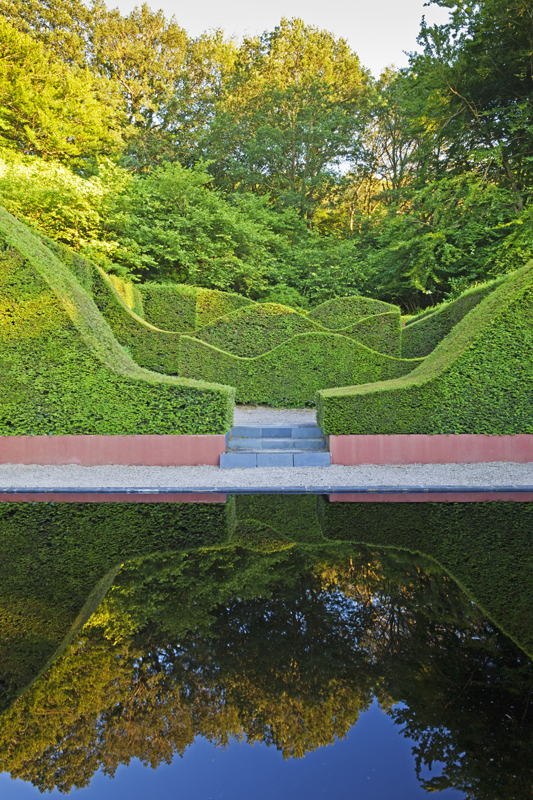 Veddw House Garden, Monmouthshire, Wales. Designed and created by Anne Wareham and Charles Hawes. July. The Reflecting Pool and Hedge Garden with view to the Coppice. Yew Hedges (Taxus baccata)